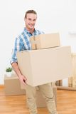 Smiling man carrying cardboard moving boxes Stock Image