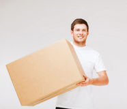Smiling man carrying carton box Royalty Free Stock Image
