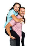 Smiling man carrying his girlfriend on back Royalty Free Stock Photos