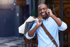 Smiling man carrying shopping bags talking on his cellphone outside Royalty Free Stock Photos