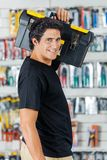 Smiling Man Carrying Toolbox On Shoulder In Store Royalty Free Stock Image