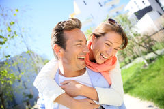 Smiling man carrying woman on his back Royalty Free Stock Photos