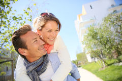 Smiling man carrying woman on his back outdoors Royalty Free Stock Image