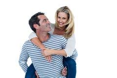 Smiling man carrying woman piggyback Royalty Free Stock Photo