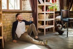 Smiling man in casual clothes on floor at home, holding cell phone in hand. Royalty Free Stock Photography