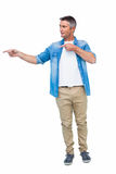 Smiling man in casual clothes pointing Royalty Free Stock Photos