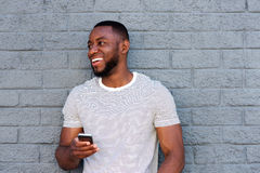 Smiling man with cell phone leaning on gray wall Stock Photography
