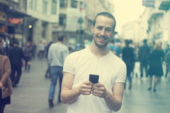 Smiling Man with cell phone walking. Smiling Man with mobile phone walking, background is blured city Royalty Free Stock Photography