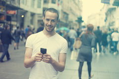 Smiling Man with cell phone walking. Smiling Man with mobile phone walking, background is blured city Stock Photography