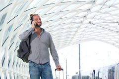 Smiling man with cell phone walking with suitcase. Portrait of smiling man with cell phone walking with suitcase Stock Images