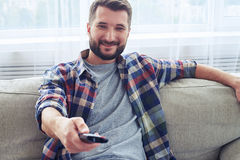 Smiling man in checkered shirt switching channel with remote con Stock Image
