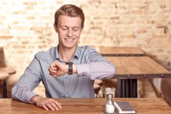 Smiling man checking time in cafe Stock Photography