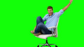 Smiling man cheering and turning on swivel chair on green screen