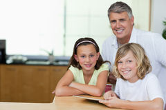 Smiling man with children and tablet Royalty Free Stock Photos