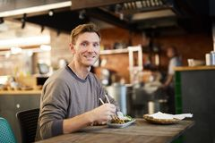 Smiling Man in Chinese Food Restaurant. Portrait of smiling young man looking at camera while enjoying Asian food in restaurant, copy space stock photography