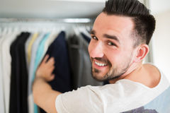 Smiling man choosing clothes. Selecting wardrobe in a good boutique. Young content man choosing jacket Stock Image
