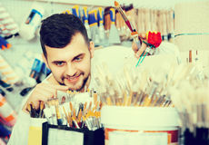 Smiling man choosing new brush for hobby. And decoration in paint supplies store Stock Photo
