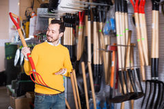 Smiling man choosing new pitchfork Royalty Free Stock Images