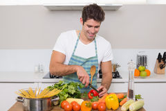 Smiling man chopping vegetables in kitchen Royalty Free Stock Photography