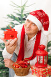 Smiling man in Christmas cap is holding small present Stock Photos