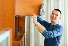 Smiling man cleaning  furniture with rag Royalty Free Stock Images