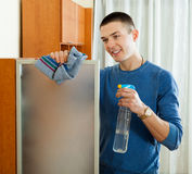 Smiling man cleaning  glass with rag and cleanser. In home Stock Photo