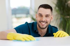 Smiling man cleaning table with cloth at home Stock Photos