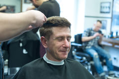 Smiling man, client in a barbershop, closing his eyes, enjoys th Stock Image