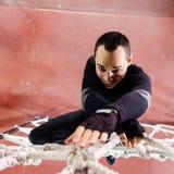 Smiling man climbing on rope net Stock Image