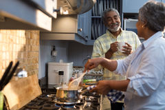 Smiling man coffee cup talking with woman preparing food. Smiling men coffee cup talking with women preparing food while standing in kitchen Royalty Free Stock Photo