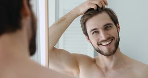 Smiling man combing hair with fingers, getting ready in bathroom.