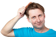 Smiling man combs his hair Royalty Free Stock Photo