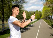 Smiling man communicating on phone by video. Profile of cheerful male waving hello to smartphone. He is speaking with somebody using earphones and camera for Stock Image