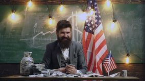 Smiling man counts money against the background of the United States flag. Large bunch of money on the table. Economy. And finance. Patriotism and freedom stock footage