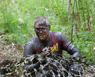 Smiling man covered with mud crawling under a camouflage net Royalty Free Stock Photography