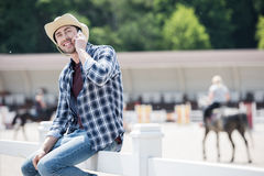 Smiling man in cowboy hat and checkered shirt sitting on wooden fence and talking on smartphone. Handsome smiling man in cowboy hat and checkered shirt sitting Stock Photos