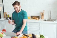 Smiling man with credit card and laptop buying goods online in kitchen. At home stock photos