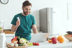 Smiling man with credit card and laptop buying goods online in kitchen. At home stock photo