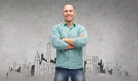 Smiling man with crossed arms. Happiness and people concept - smiling man with crossed arms and city drawing in the back stock photo