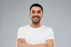 Smiling man with crossed arms over gray background Royalty Free Stock Photography