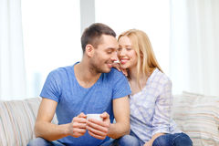 Smiling man with cup of tea or coffee with wife. Love, family, healthy food and happiness concept - smiling men with cup of tea or coffee with wife or girlfriend Stock Image