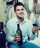 Smiling man customer holding glass and bottle of wine Stock Photo