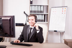 Smiling man from Customer service support working in the office Stock Image