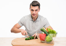 Smiling man cutting cucumber Royalty Free Stock Photo