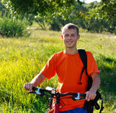 Smiling man cyclist among the green scenery Stock Images