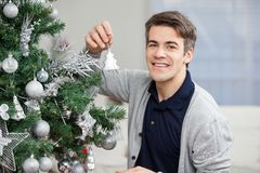 Smiling Man Decorating Christmas Tree Stock Photos