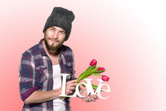 Smiling man with decorative word love and red tulips Royalty Free Stock Image