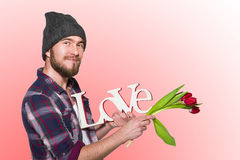 Smiling man with decorative word love and red tulips Royalty Free Stock Photos