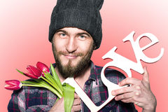 Smiling man with decorative word love and red tulips Royalty Free Stock Images