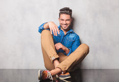 Smiling man in denim shirt sitting legs crossed in studio backgr Stock Photo